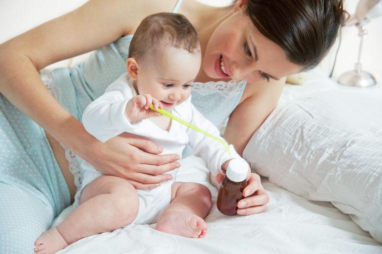 Bebé xogar con botella de xarope e culler